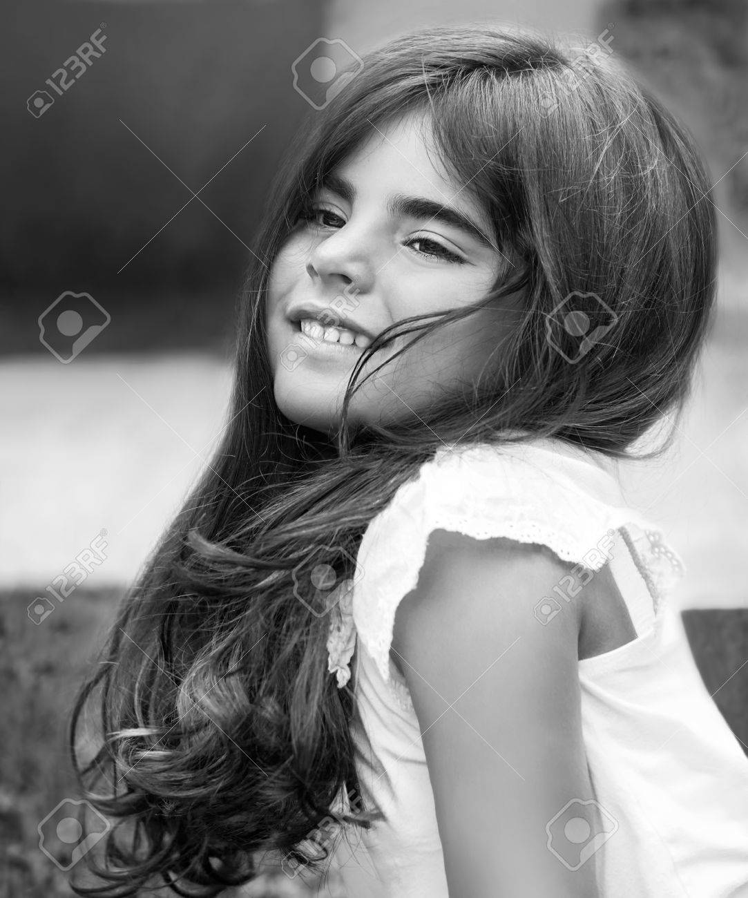Fashion black and white photo of a beautiful little girl having fun in the park
