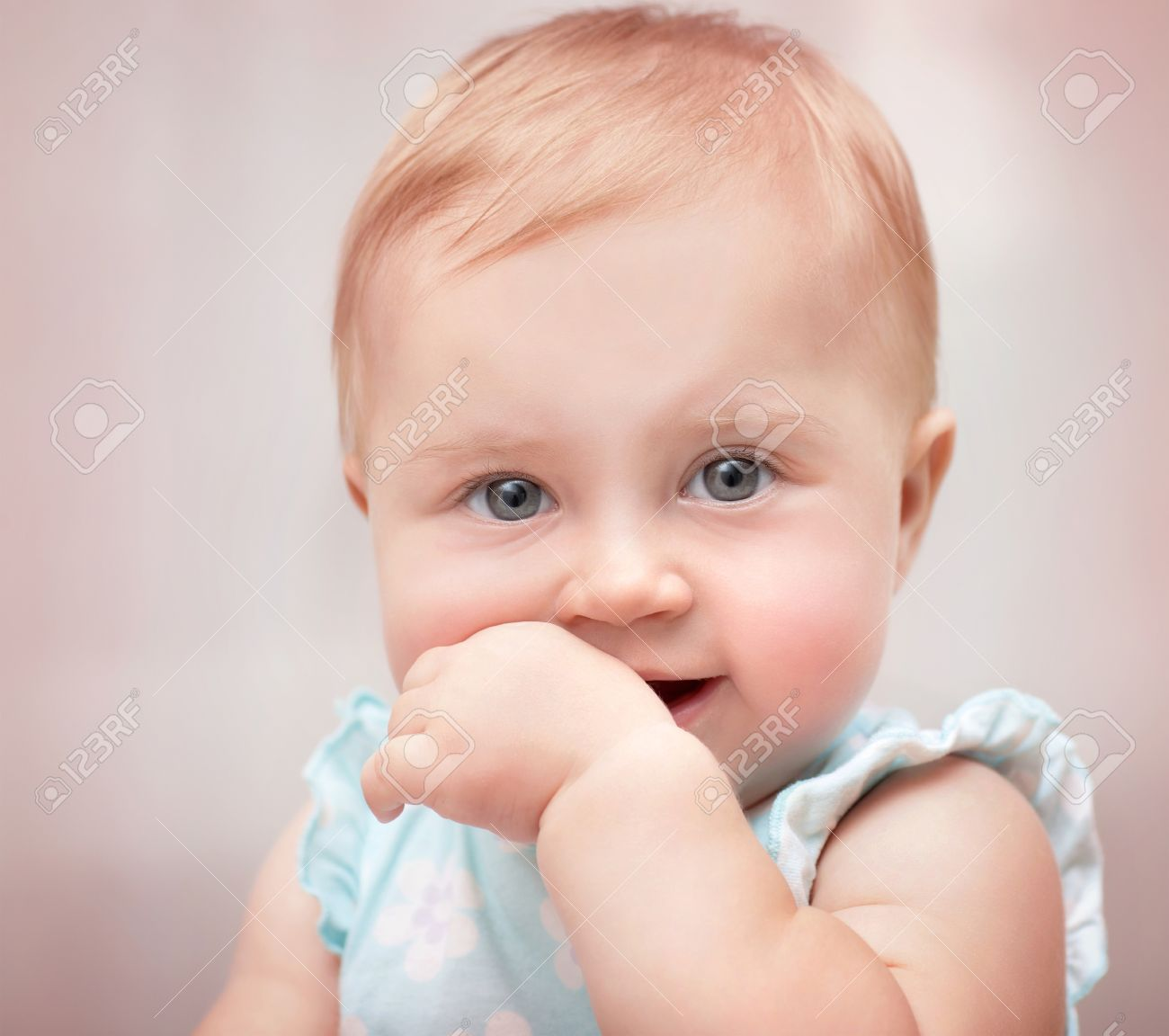 closeup portrait of a beautiful little baby girl with hand in