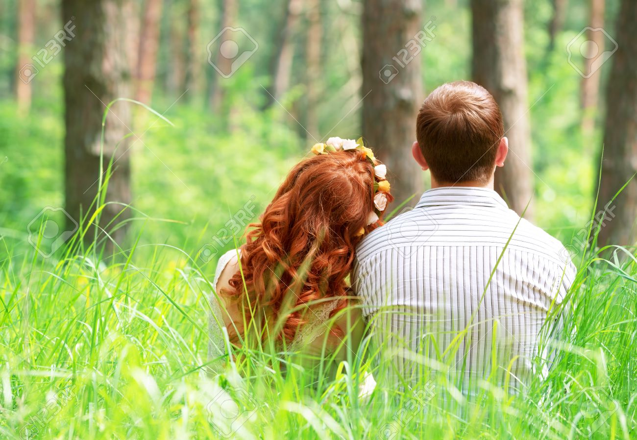 Back side of cute peaceful couple sitting on grass in the park relaxing outdoors