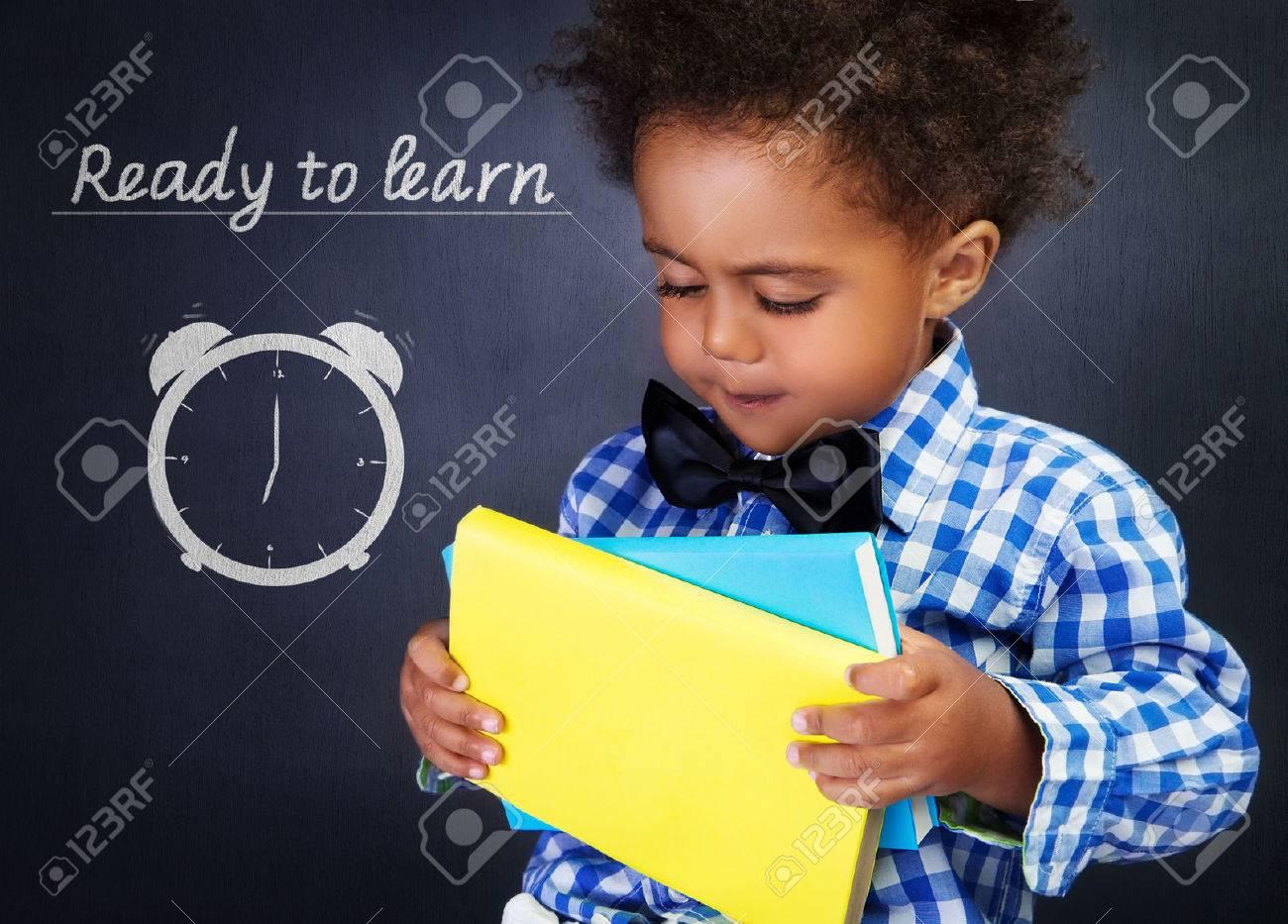 Cute african american boy with books in hands on blackboard background, adorable preschooler ready to learn in elementary school - 44322152