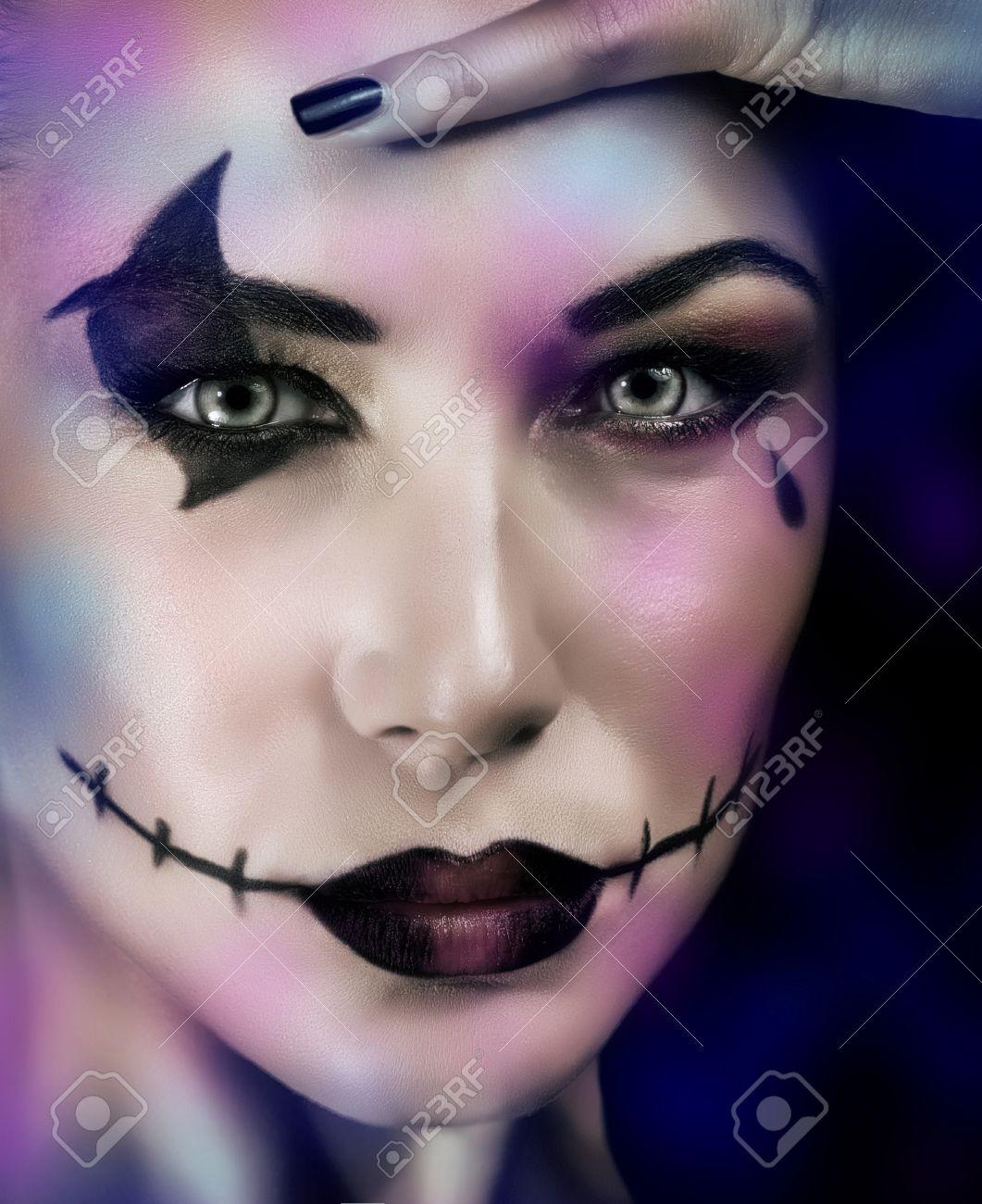 Foto de archivo , Primer retrato de mujer con maquillaje para la fiesta de Halloween sobre fondo azul oscuro, bruja aterradora, zombi muertos mira