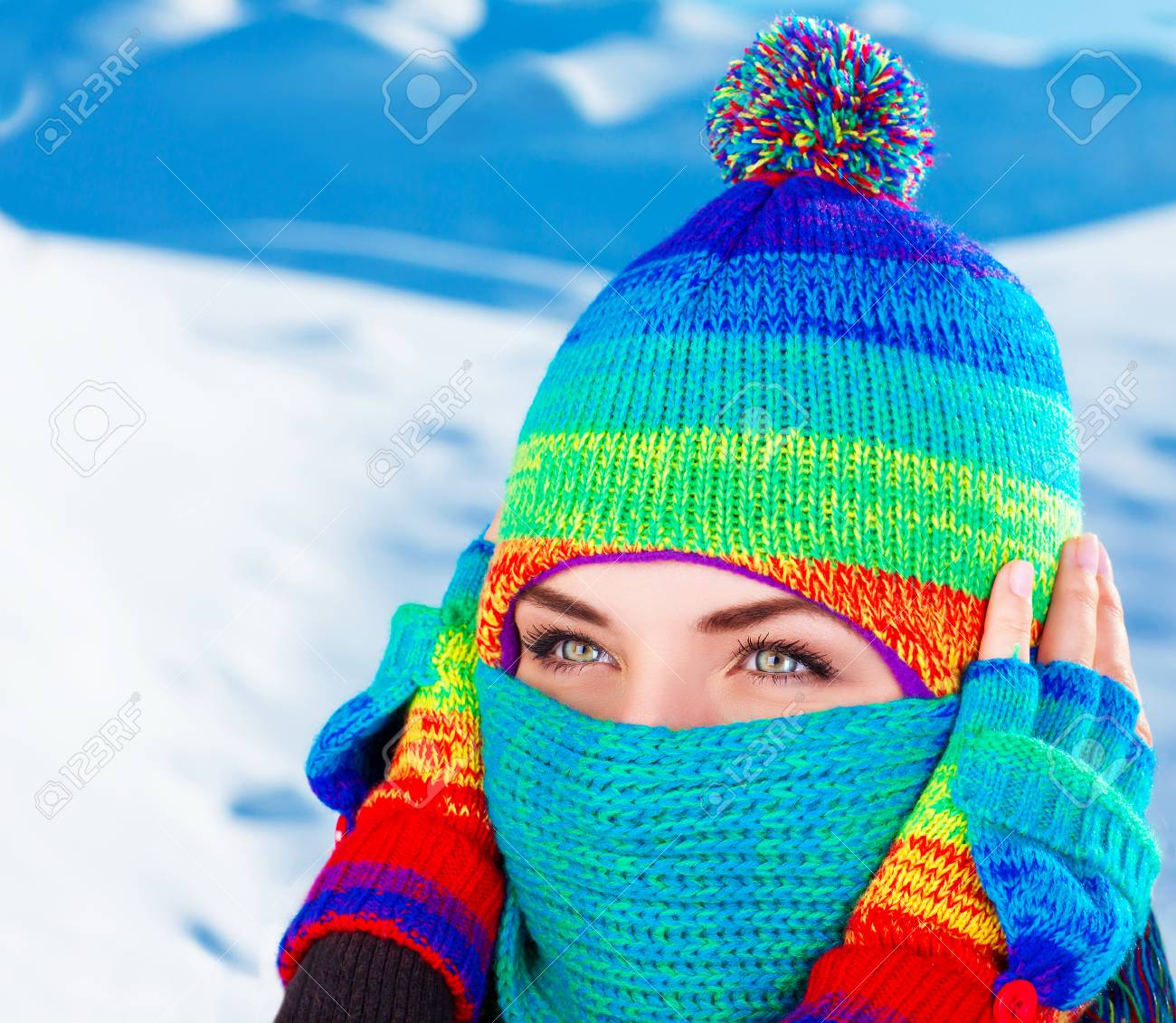 Closeup portrait of cute female wearing stylish colorful hat and covering  half of face with scarf 00c95aed9f5