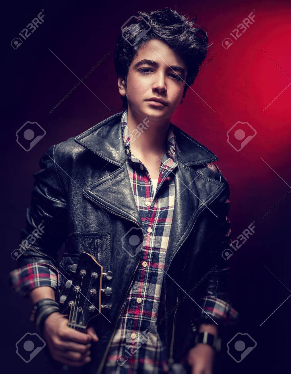 1b50cea5f Attractive teen guy posing with guitar over dark red background,..