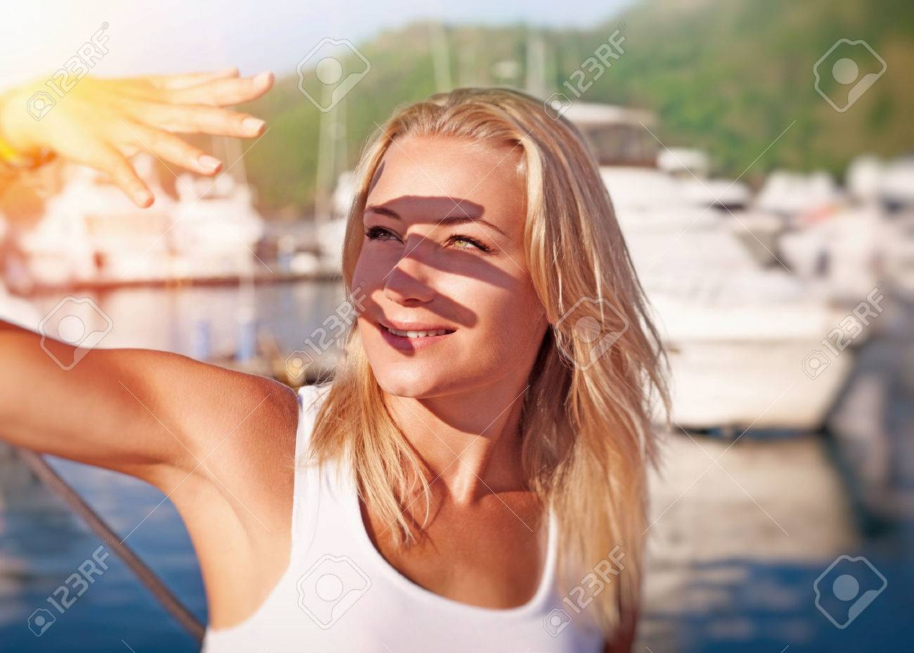 Portrait of a beautiful blond girl covering face by hand of bright sun light, spending weekend on the yacht, happy summer vacation - 57764867