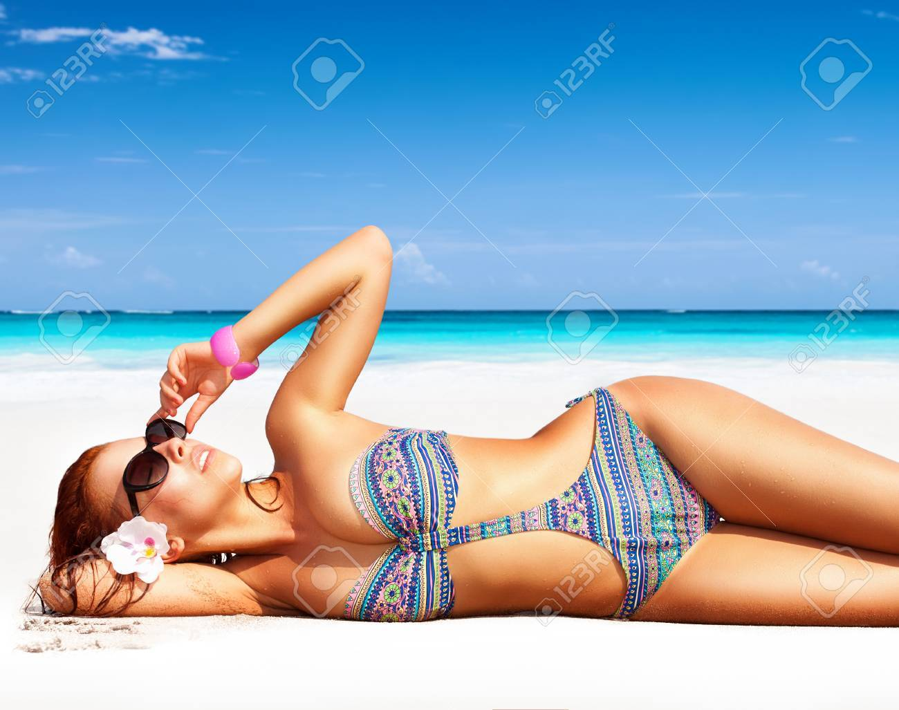 Beautiful woman on the beach, lying down on clean white sandy coast and with pleasure sunbathing, summer vacation on a tropical islands - 60168777