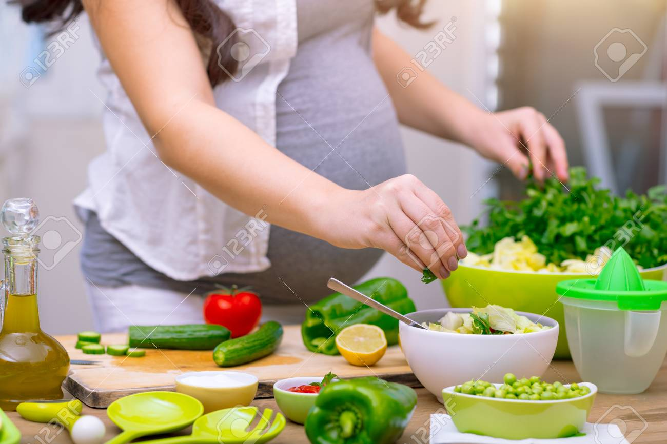Happy pregnant woman cooking at home doing fresh green salad happy pregnant woman cooking at home doing fresh green salad eating many different vegetables forumfinder Image collections