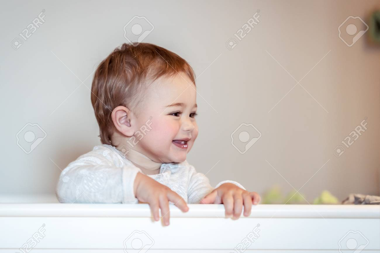 Portrait Of A Cute Little Baby Boy At Home Standing In The Crib