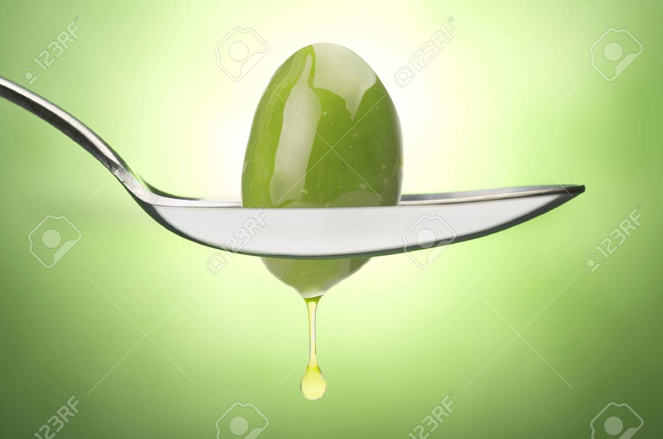 72aeb9a1c0d8 Iron Spoon with olive oil close up on a green Stock Photo - 25071822