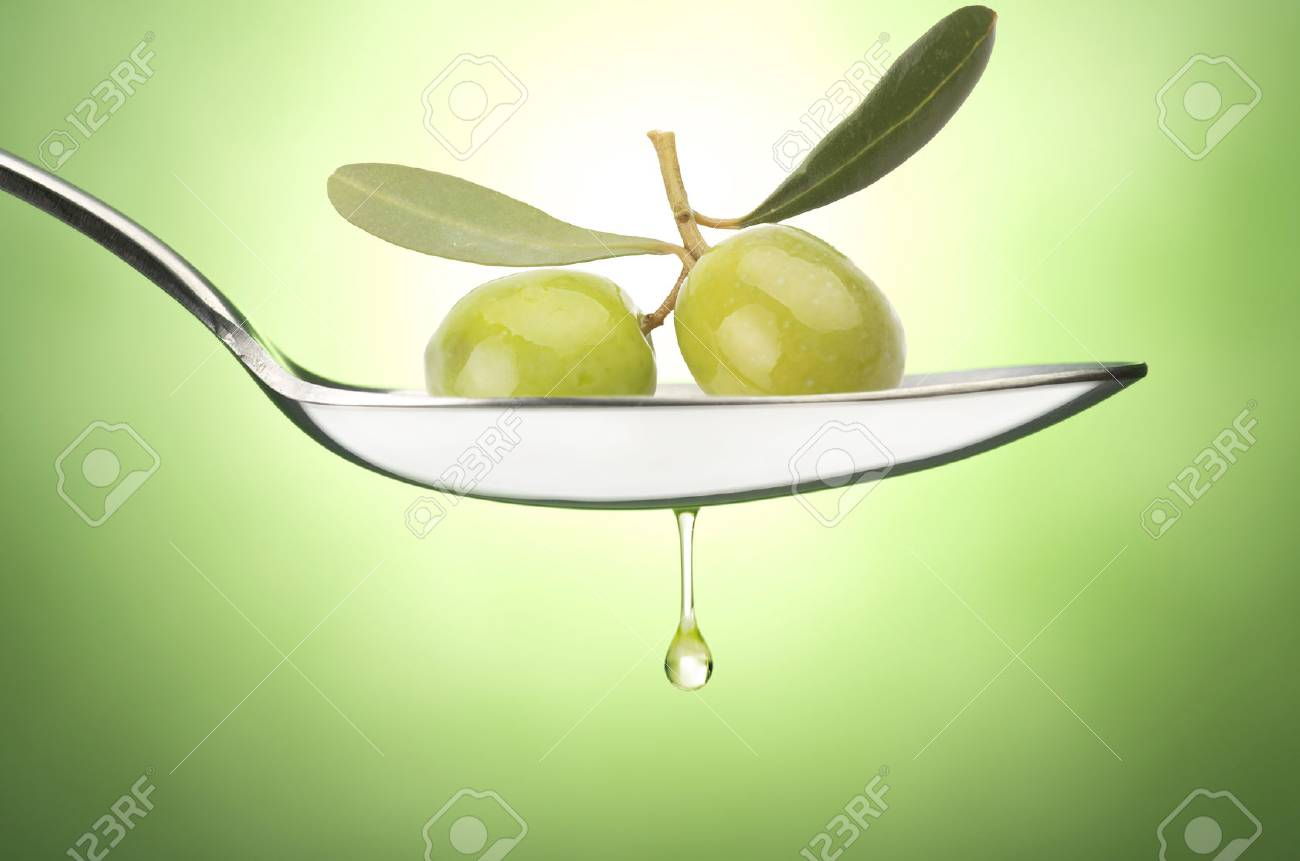 edaba1f26e66 Iron Spoon with olive oil close up on a green Stock Photo - 25071856