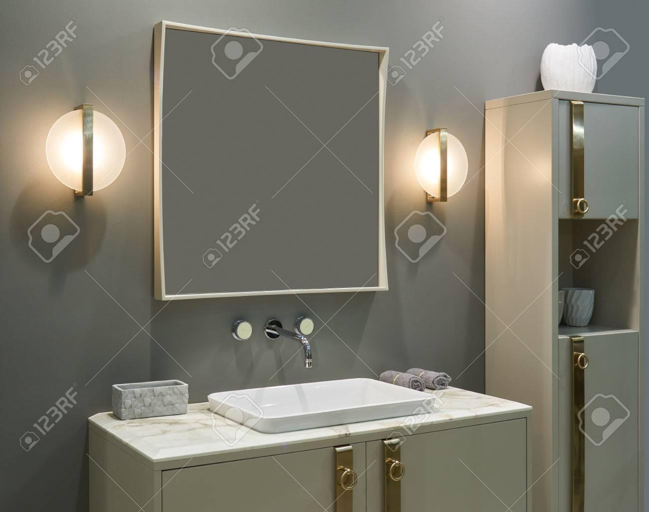 Salle de bains intérieure de luxe: mitigeur mural, lavabo encastré, grand  miroir, lampes électriques et meubles