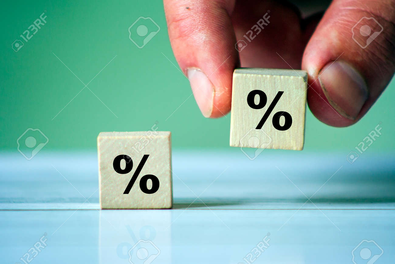 Business man Hand putting wood cube block with percentage symbol icon. Interest rate, financial, ranking and mortgage rates. - 157011127