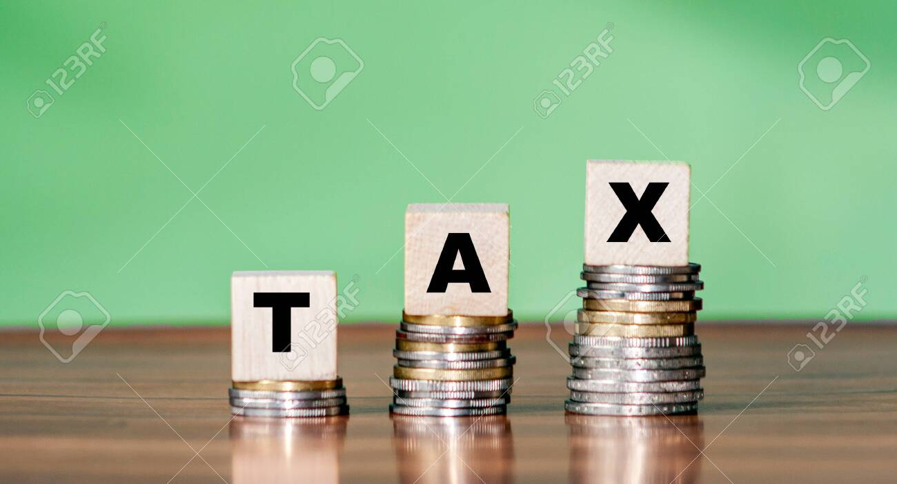 Tax word on wooden cube shape stacked on steps with coins - 156744402
