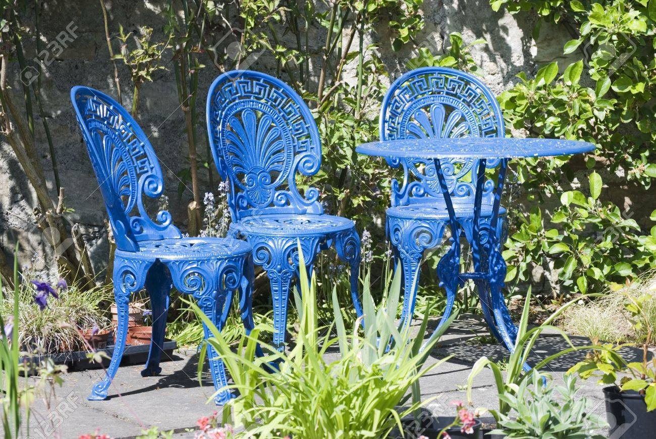 a horizontal image of blue painted wrought iron garden furniture..