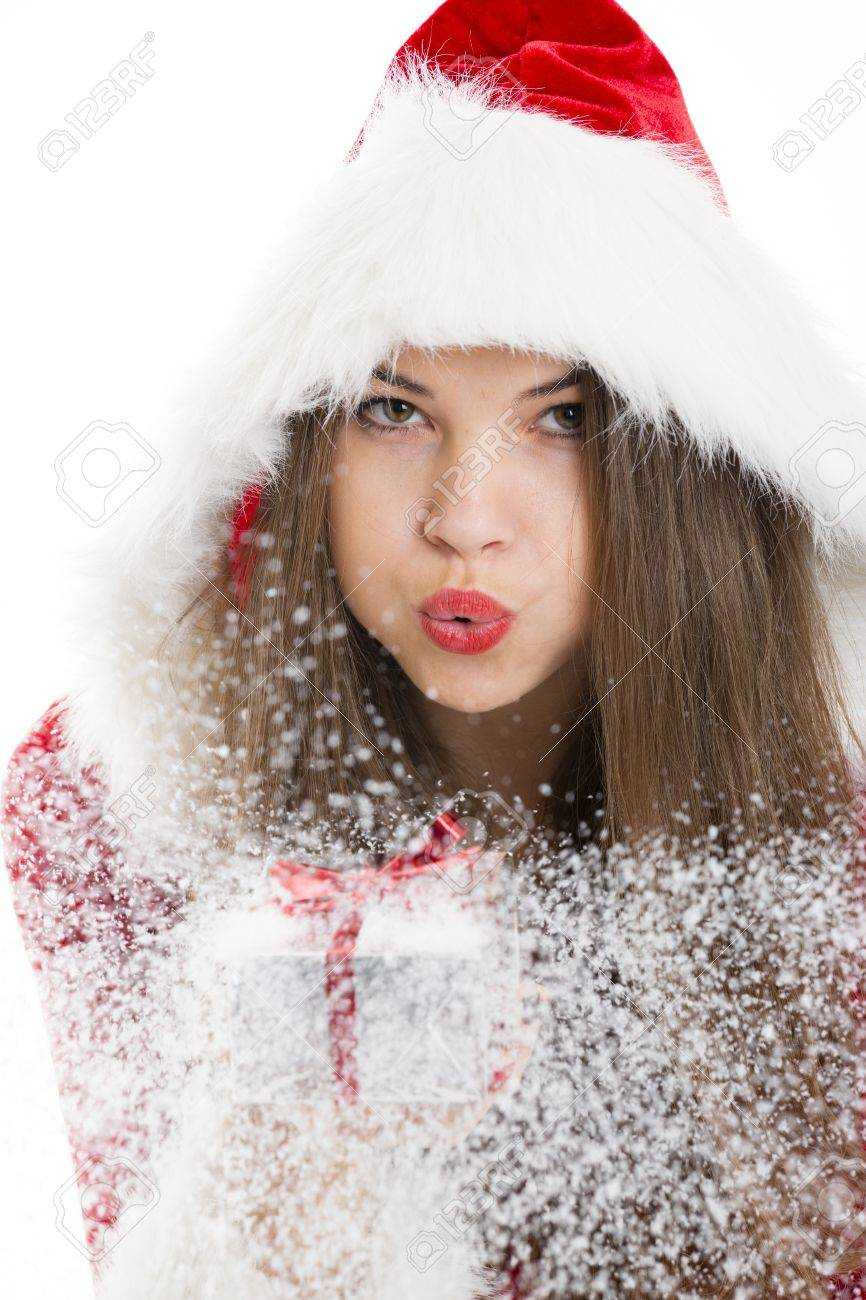 Portrait of beautiful Santa girl blowing snow off the silver Christmas gift box in her hand Stock Photo - 16791123