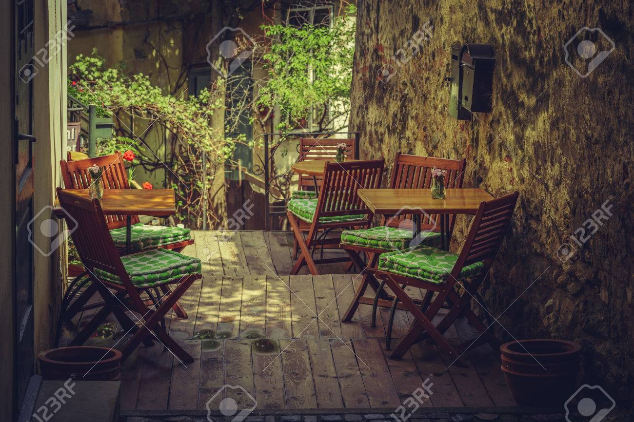 Homey outdoor cafe terrace setting with wooden chairs and tables in a shady vintage place. & Homey Outdoor Cafe Terrace Setting With Wooden Chairs And Tables ...