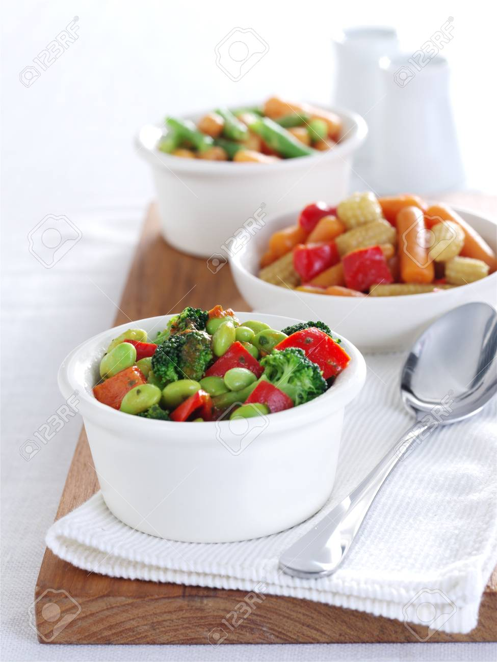 Bean Salads in white china bowls on a wooden board Stock Photo - 9856362