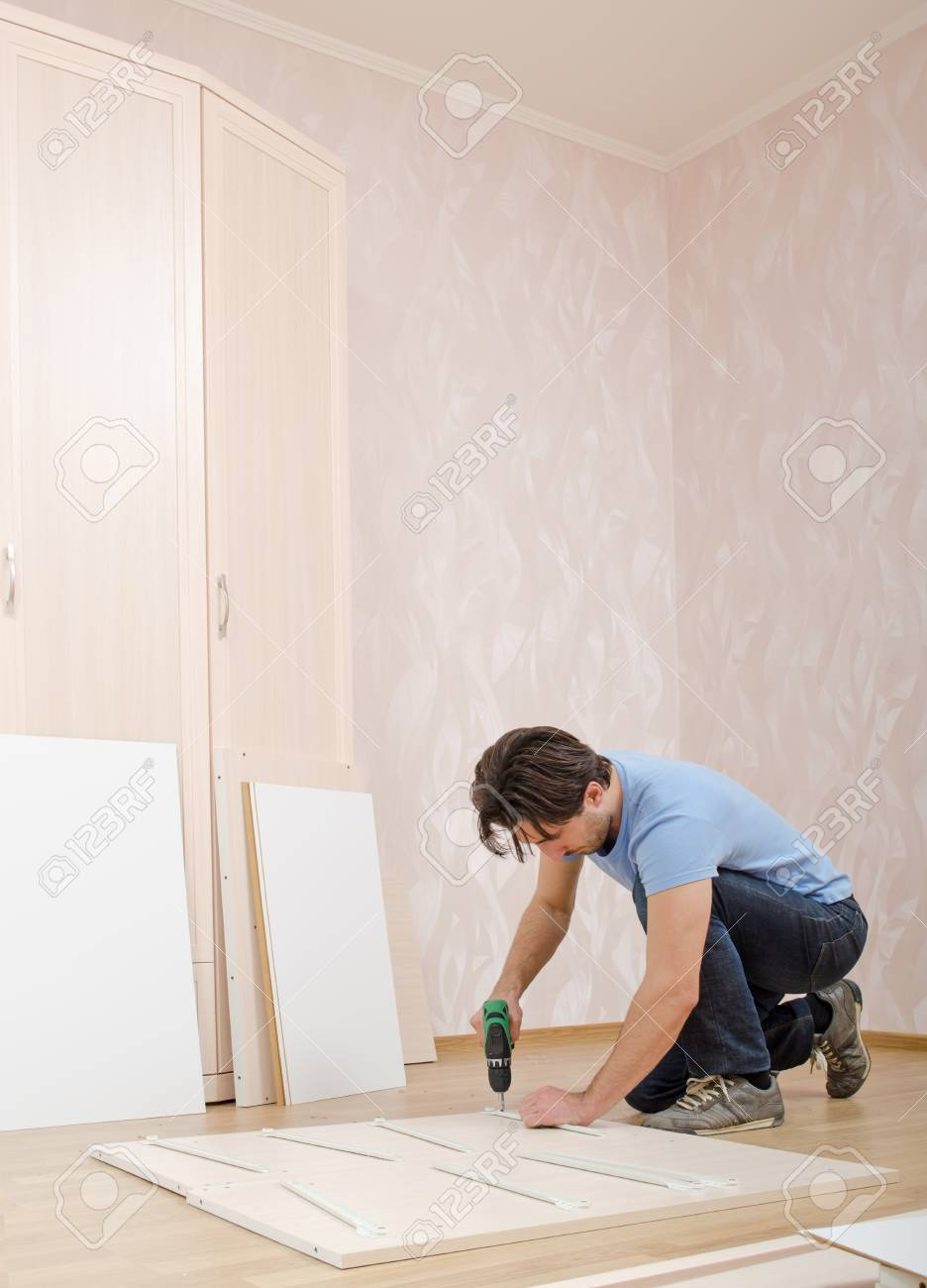 man by drill to twist screw furniture assembly Stock Photo - 16904772
