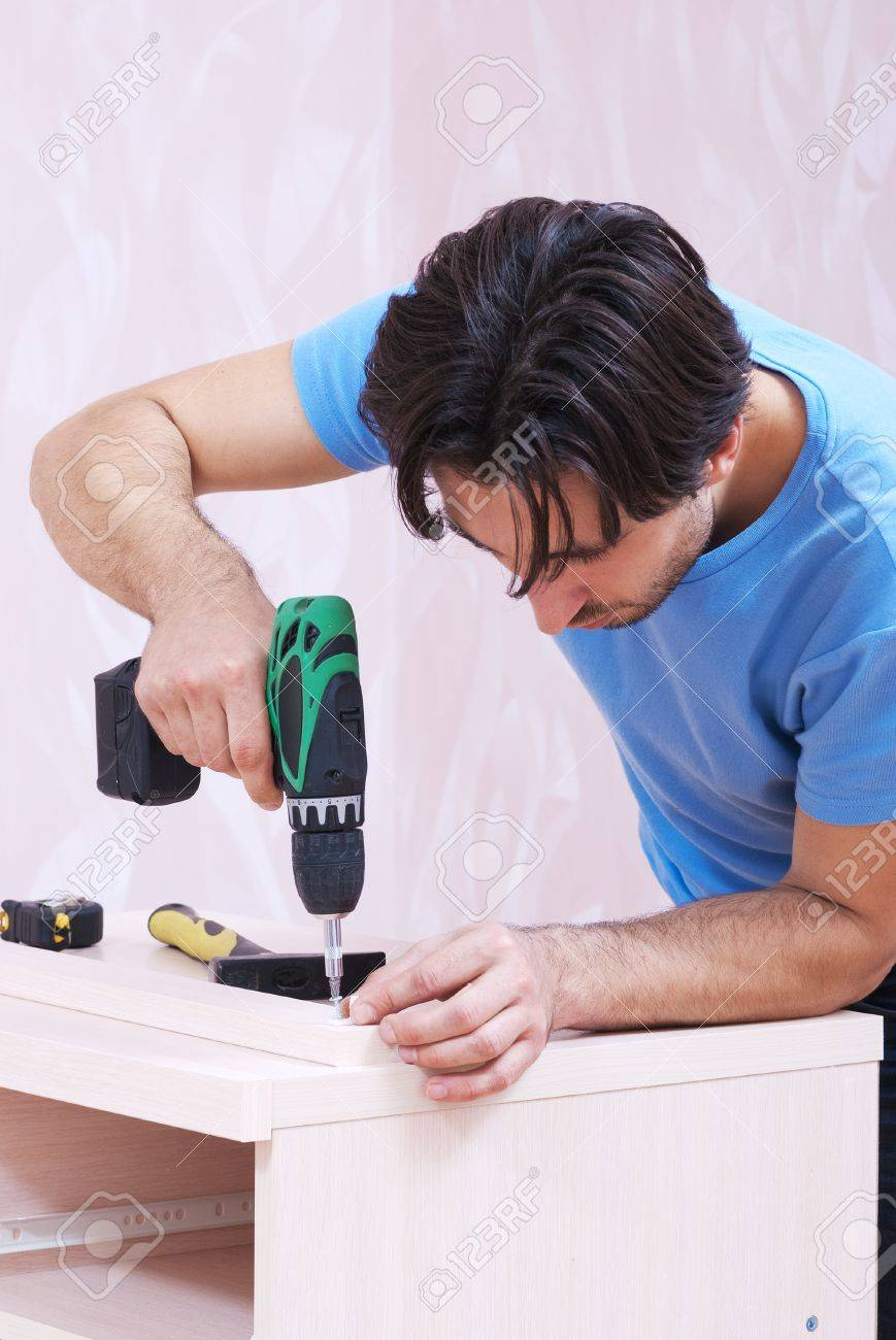 Carpenter collects wood furniture with a drill Stock Photo - 19379625
