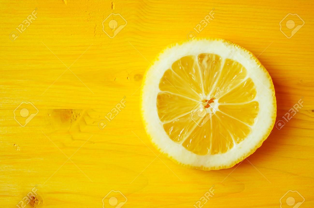 lemon slice on a yellow table closeup top view