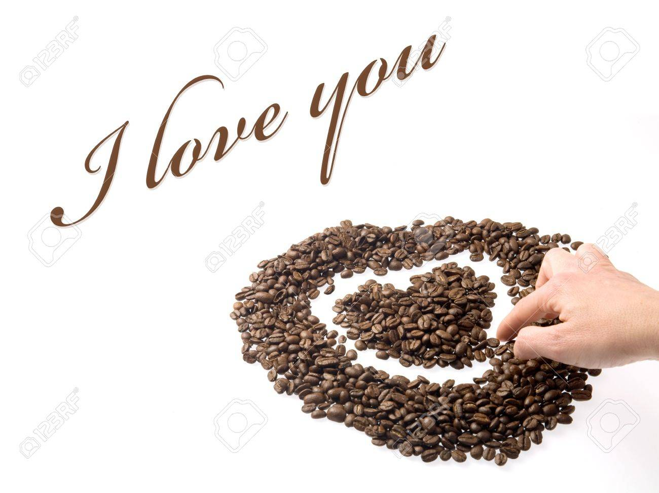 Hand designing a heart with coffee beans as a symbol of love hand designing a heart with coffee beans as a symbol of love stock photo biocorpaavc Images