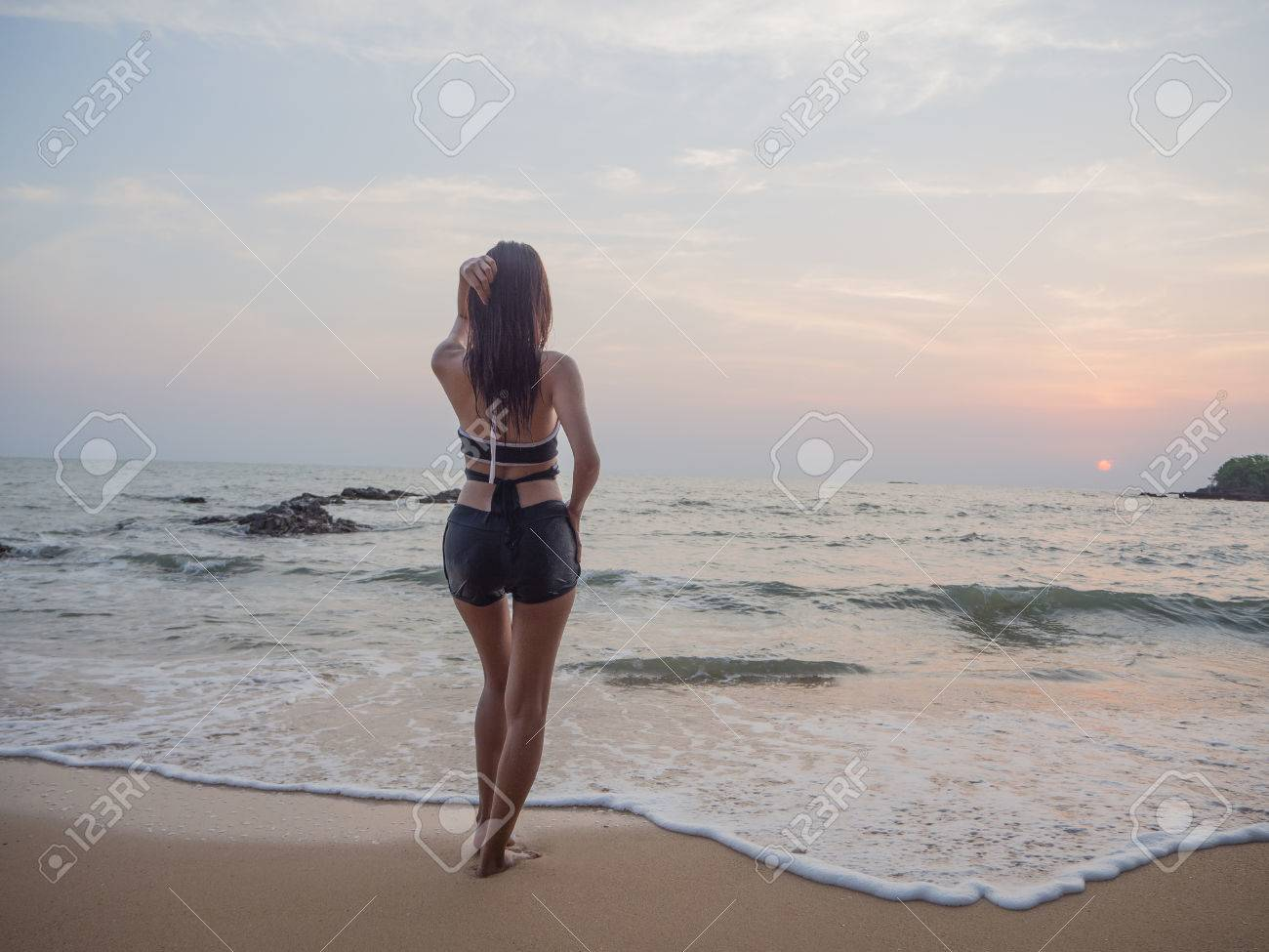 Female stand alone girl alone in the water, watery beach on the windy day.