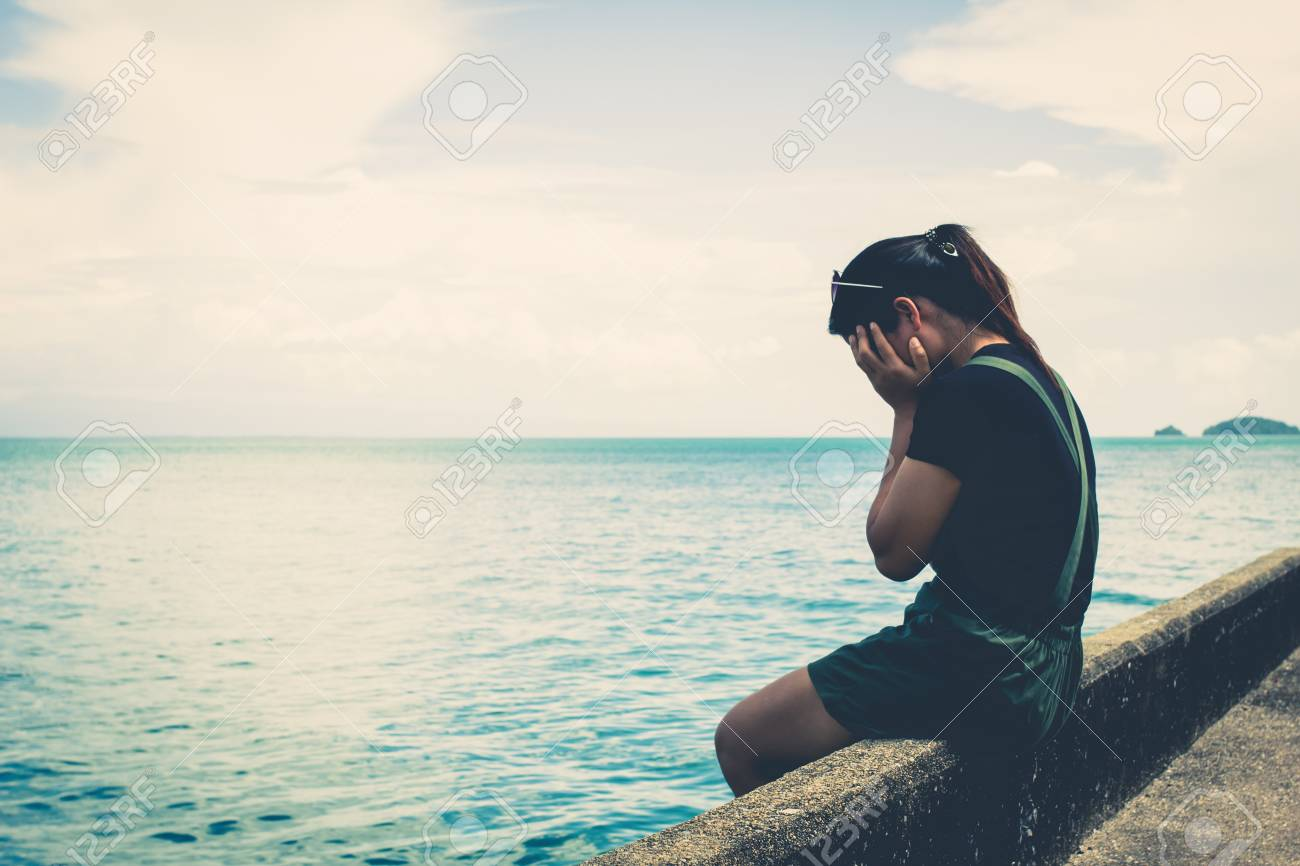 the girl sitting alone at the sea stock photo picture and royalty