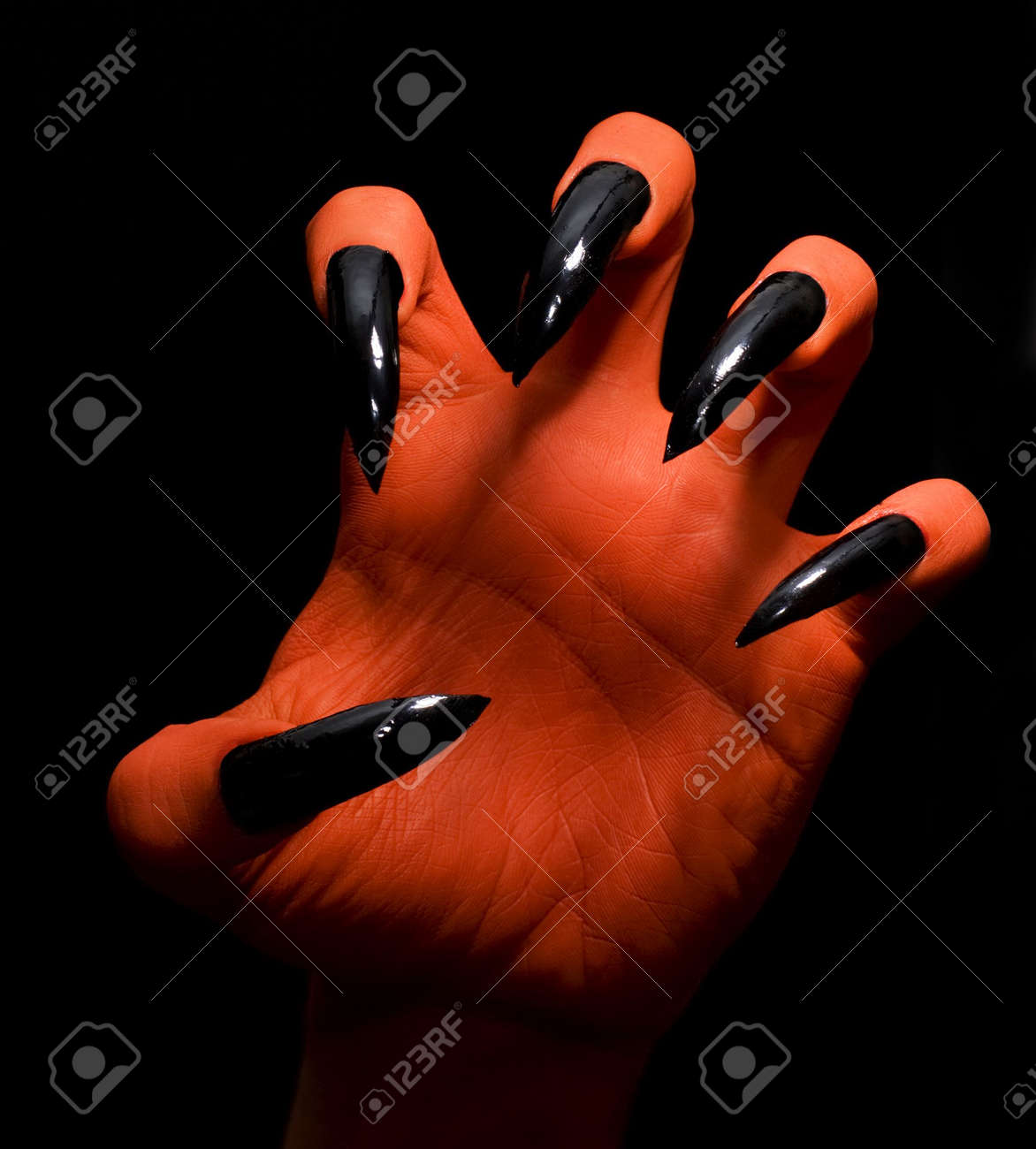 red spooky devil hand on a dark background catching you stock photo