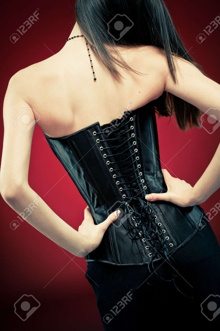 Modern style gothic woman in black leather corset on red vampire background. Hands on waist, standing back to camera. Stock Photo - 6534157