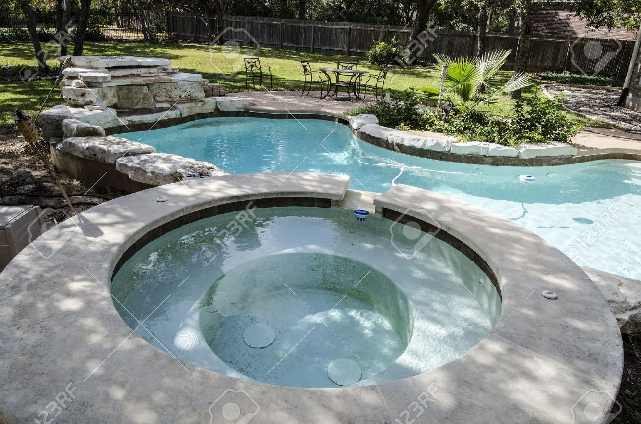 large upscale hot tub attached to kidney shaped swimming pool stock photo