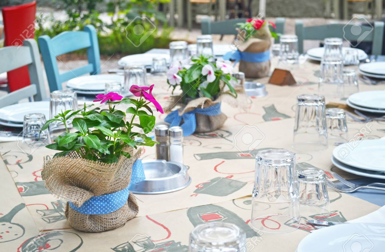 Table Decorated With Blooming Flower Pots At A Greek Restaurant