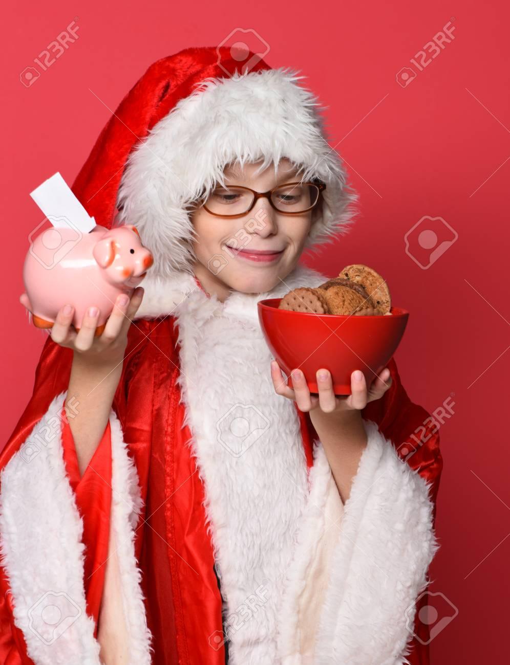 Chico Joven De Papá Noel Lindo Con Los Vidrios En El Suéter Navidad Y El  Sombrero De La Navidad Nuevo Año Que Sostienen Banco De Cerdo Alcancía De  Color ... d9ad247ac08