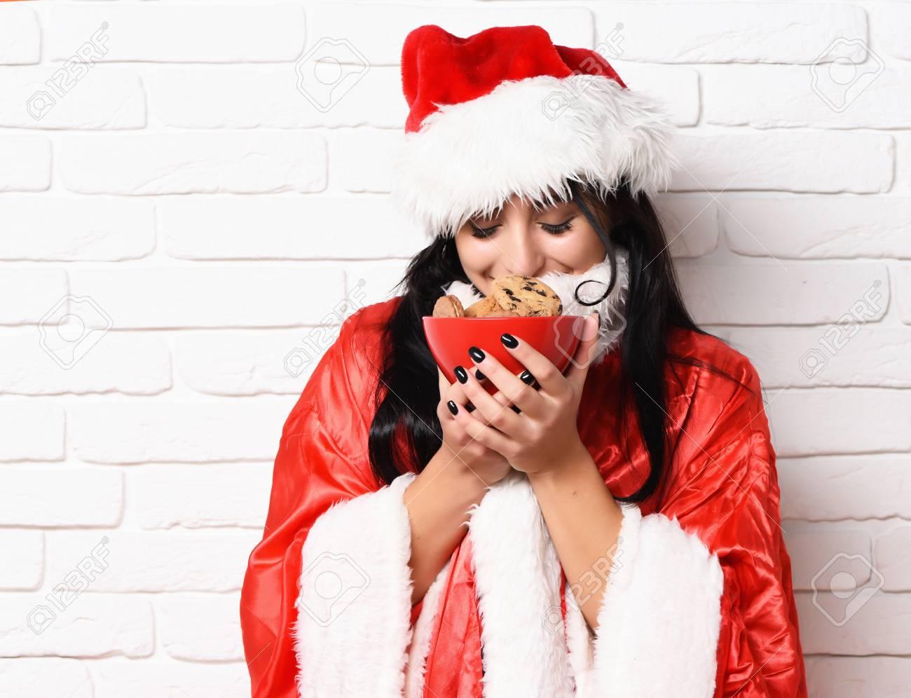 Bastante Linda Chica De Santa O Sonriente Mujer Morena En Año Nuevo Suéter  Y Sombrero Sosteniendo Y Oliendo Navidad O Navidad Galletas De Cadera De ... aebbbf5e64a