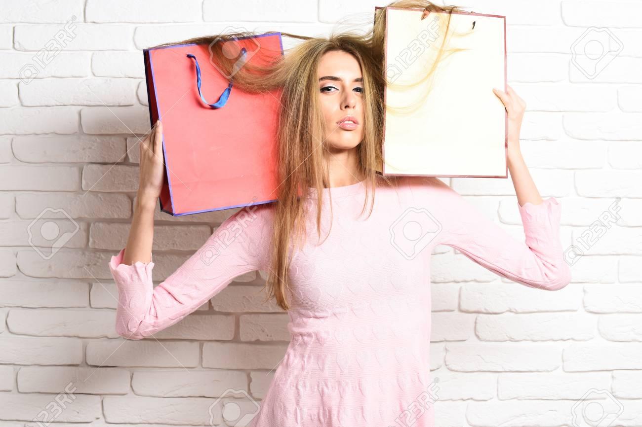 Joven Mujer Bonita Sexy O Niña Con Cabello Rubio Largo Hermoso Vestido Rosa Y Maquillaje De Moda Con Bolsas De Colores Sobre Los Hombros En El Fondo