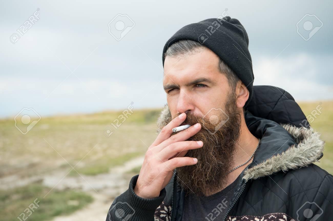 Homme qui fume. jeune homme barbu hipster fumer cigarette en chapeau et  veste à la montagne et ciel nuageux sur fond naturel, espace copie