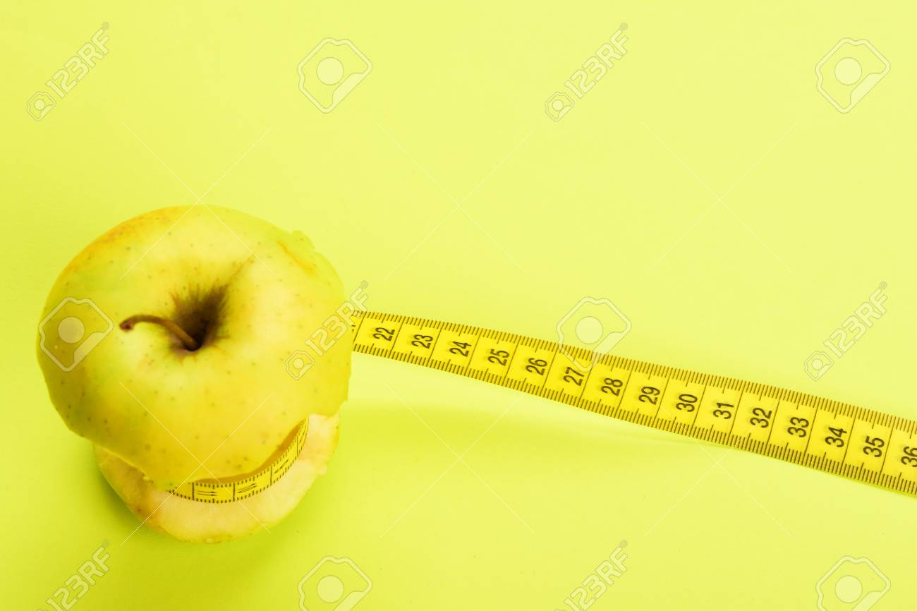 Tying of apple with yellow tape measure on light warm yellow stock stock photo tying of apple with yellow tape measure on light warm yellow background aloadofball Images