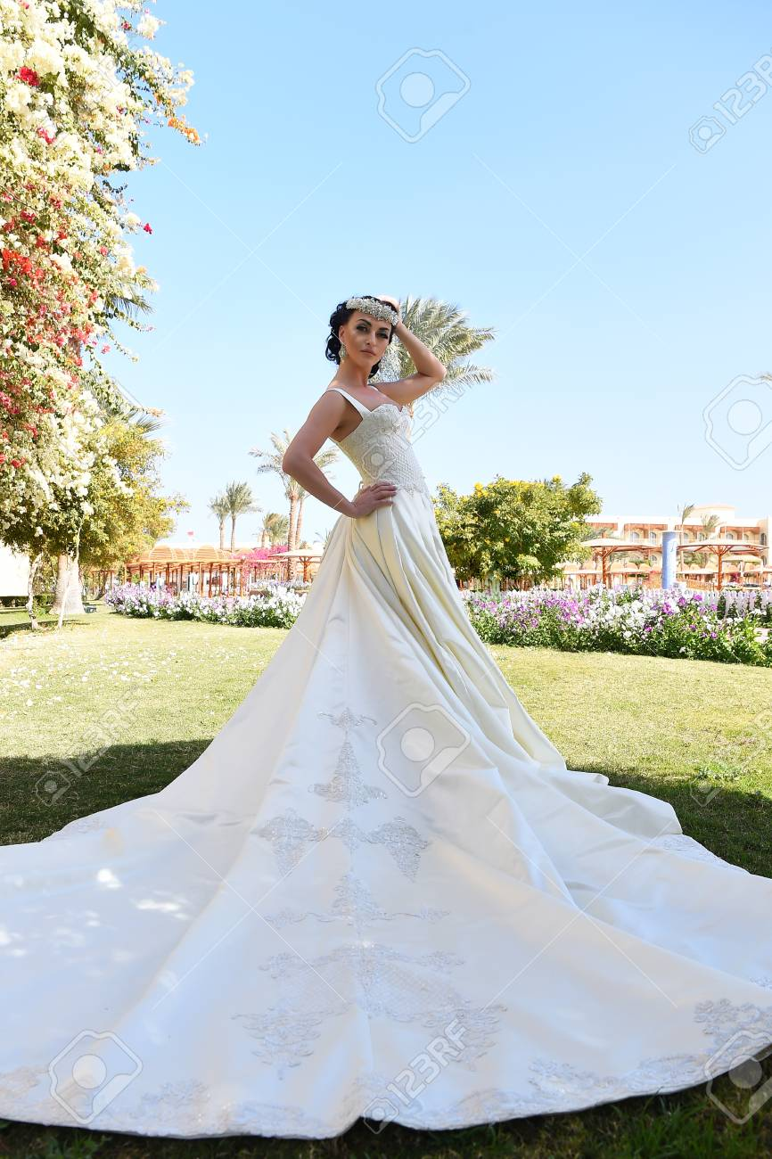 9236e560b02f Archivio Fotografico - Vista integrale di bella giovane sposa castana  sensuale in vestito da sposa bianco lungo che sta l estate vicina delle  palme ...