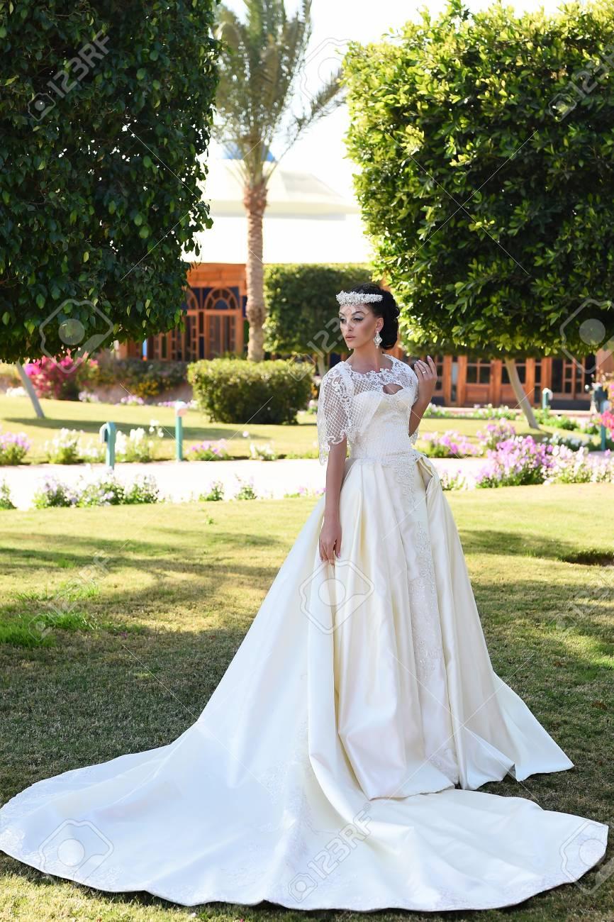 Femme au mariage. jolie femme en robe de mariée de couleur blanche, fille a  maquillage à la mode et les cheveux debout en plein air été ensoleillé sur