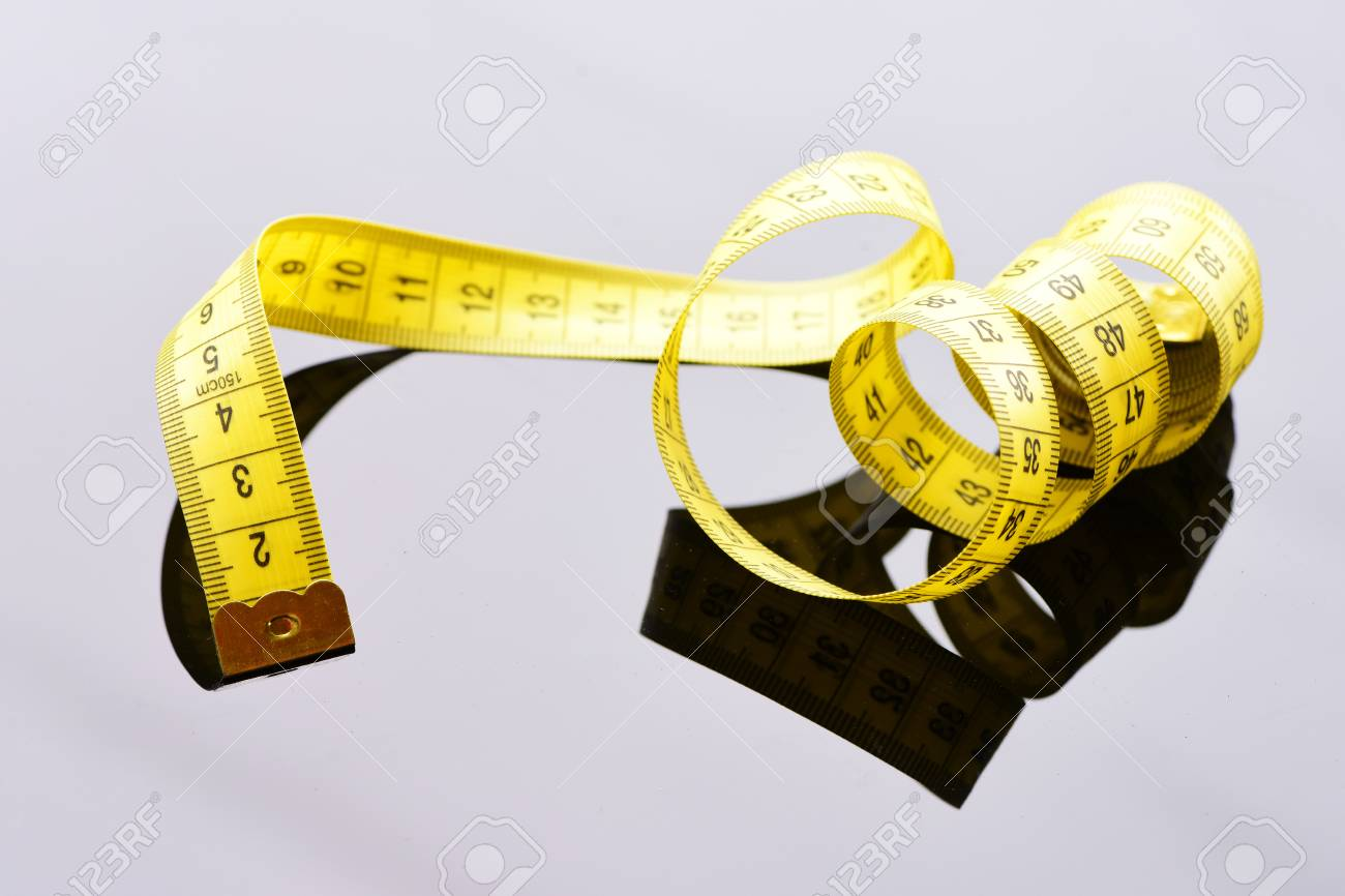 Roll of yellow tape for measuring untwisted curly on light grey roll of yellow tape for measuring untwisted curly on light grey surface with reflection stock photo aloadofball Images
