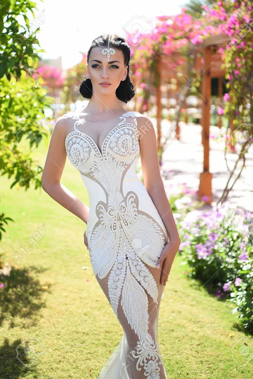 Fille ou jolie femme en robe de mariée de couleur blanche, fille a  maquillage à la mode et les cheveux debout en plein air été ensoleillé sur  fond