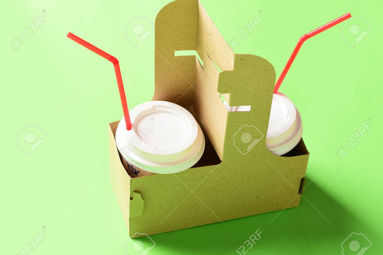 017b00e7156 Cardboard bag with two takeaway coffee cups with white covers and red  straws, light green