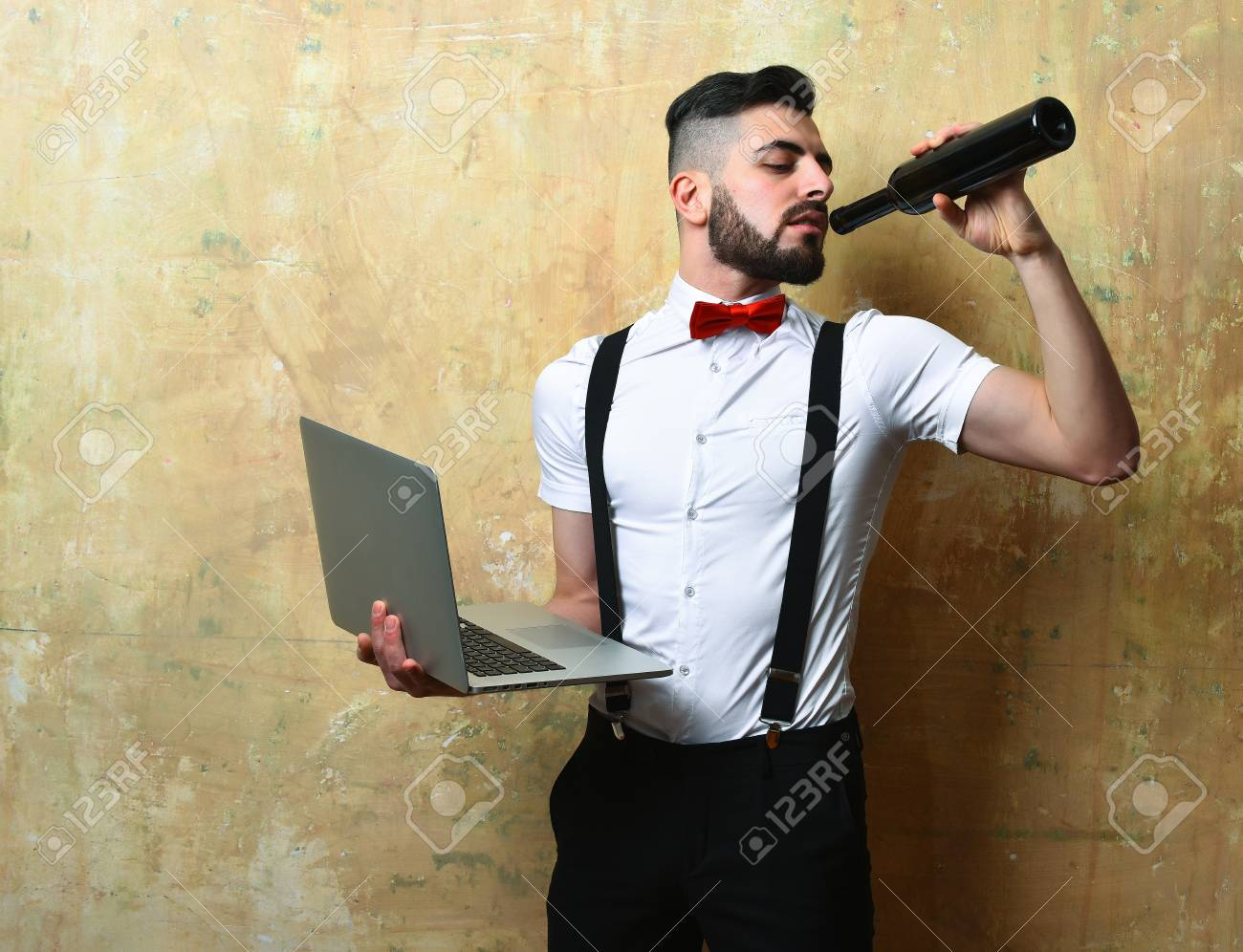 442048b962044c Man with dark beard in white shirt, suspenders and red bow tie drinks wine  and