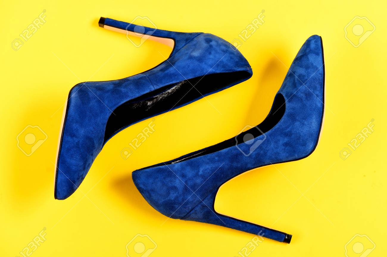 0d8b631459d Shoes in dark blue color. High heel footwear isolated on yellow background.  Elegance and fashion concept. Pair of fancy suede female shoes