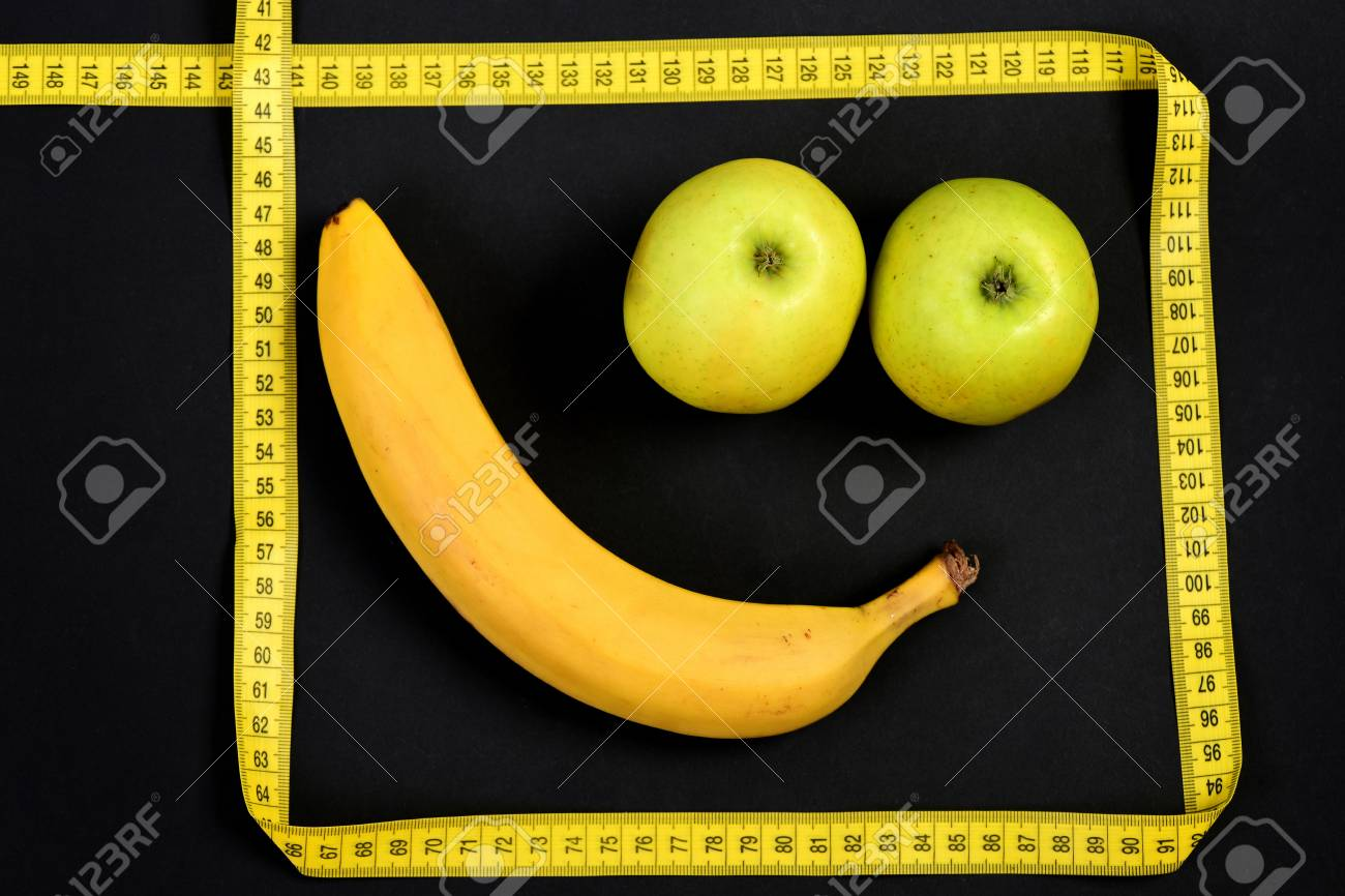 Minimalistic Art Composition With Funny Smile Made Of Banana And Green Apples For Mouth And Eyes