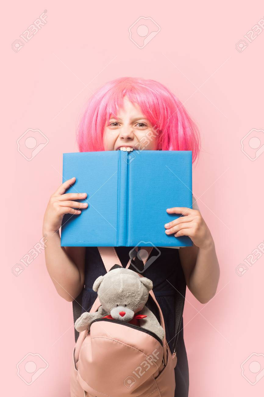 Girl with backpack and toy bites big blue book. Schoolgirl with pink wig  isolated on 7e3553e0a