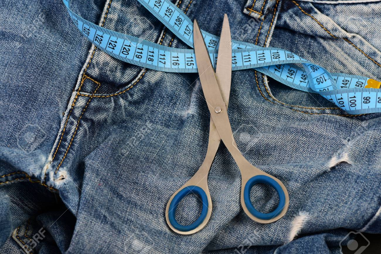 tailors tools on denim textile making clothes and design concept