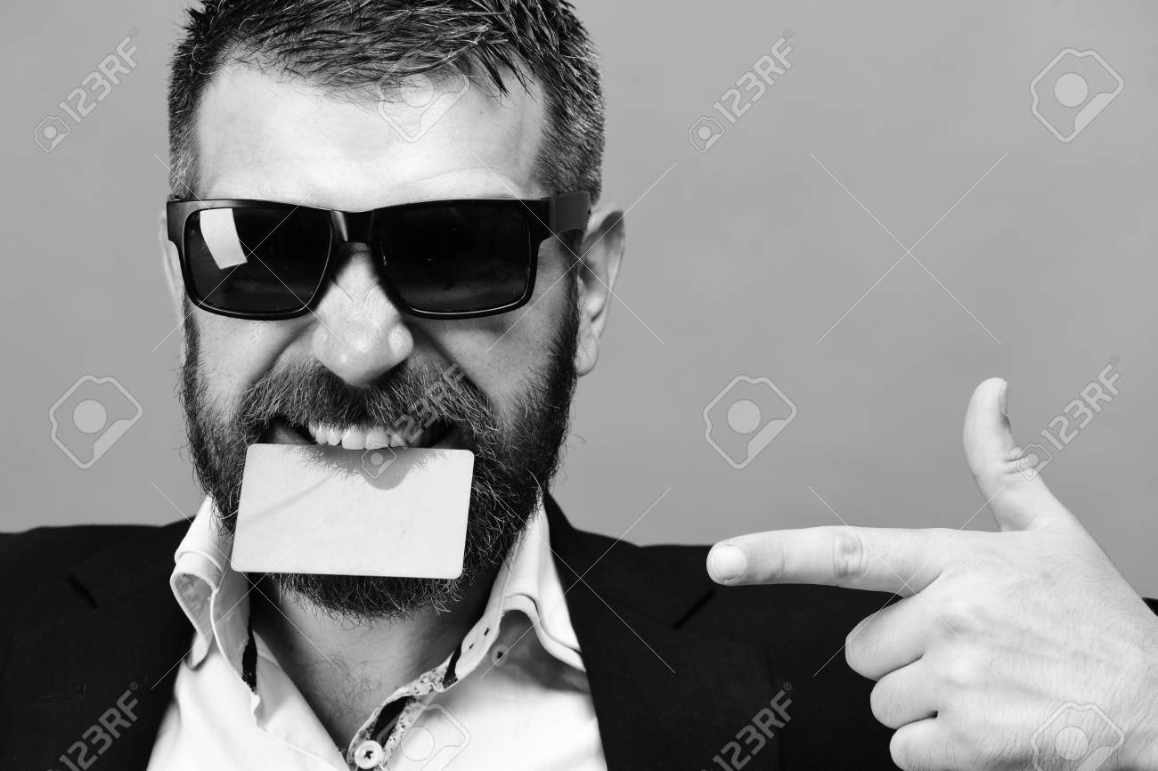 Man With Dark Beard Holds Green Business Card In Teeth. Guy With ...