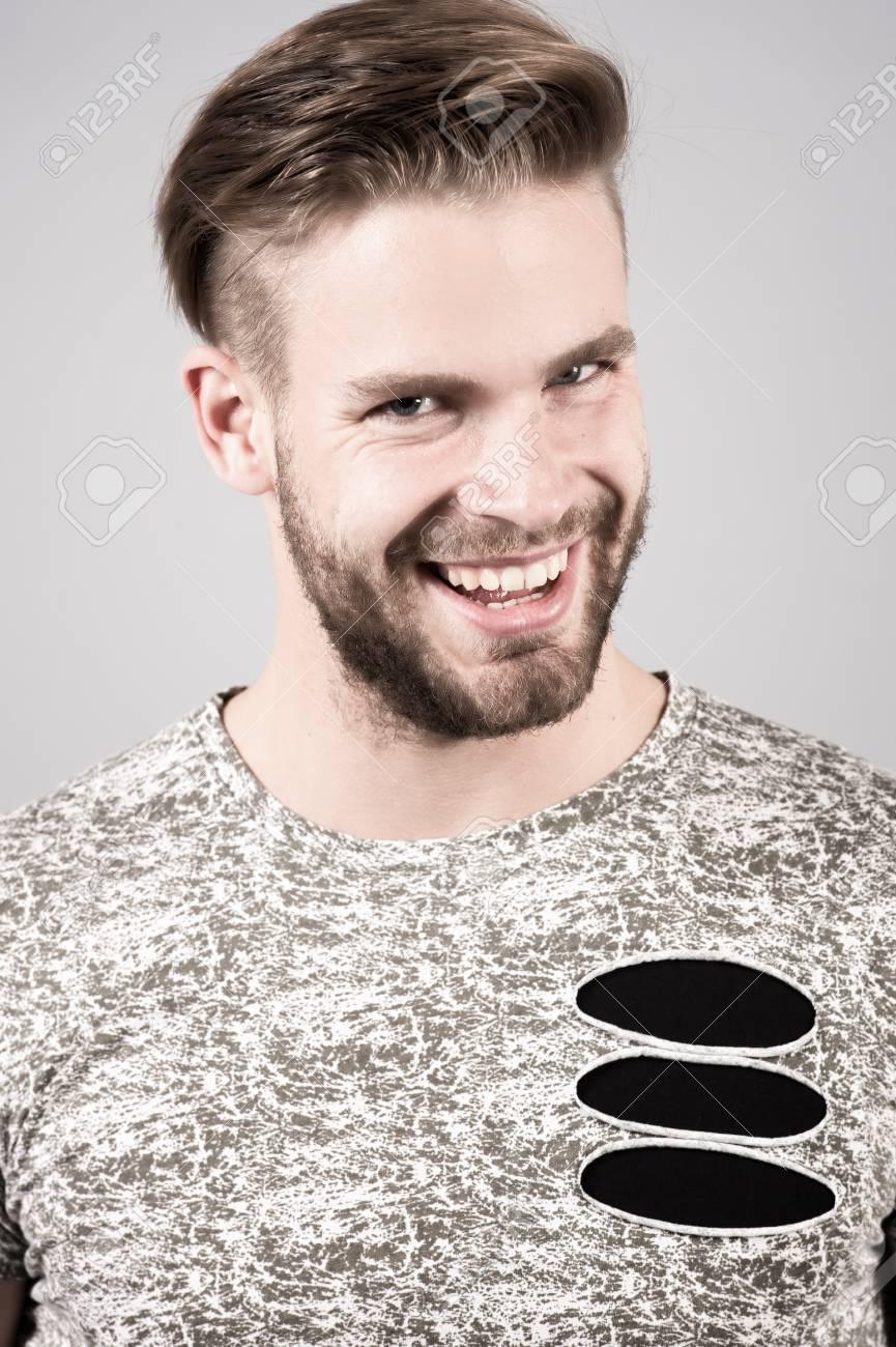 Homme A La Barbe Sur Le Visage Non Rase Et Les Cheveux Elegant En Tshirt Sourire Sur Fond Gris Mode Style Tendance Salon De Coiffure Salon De Coiffure Toilettage Concept De Beaute
