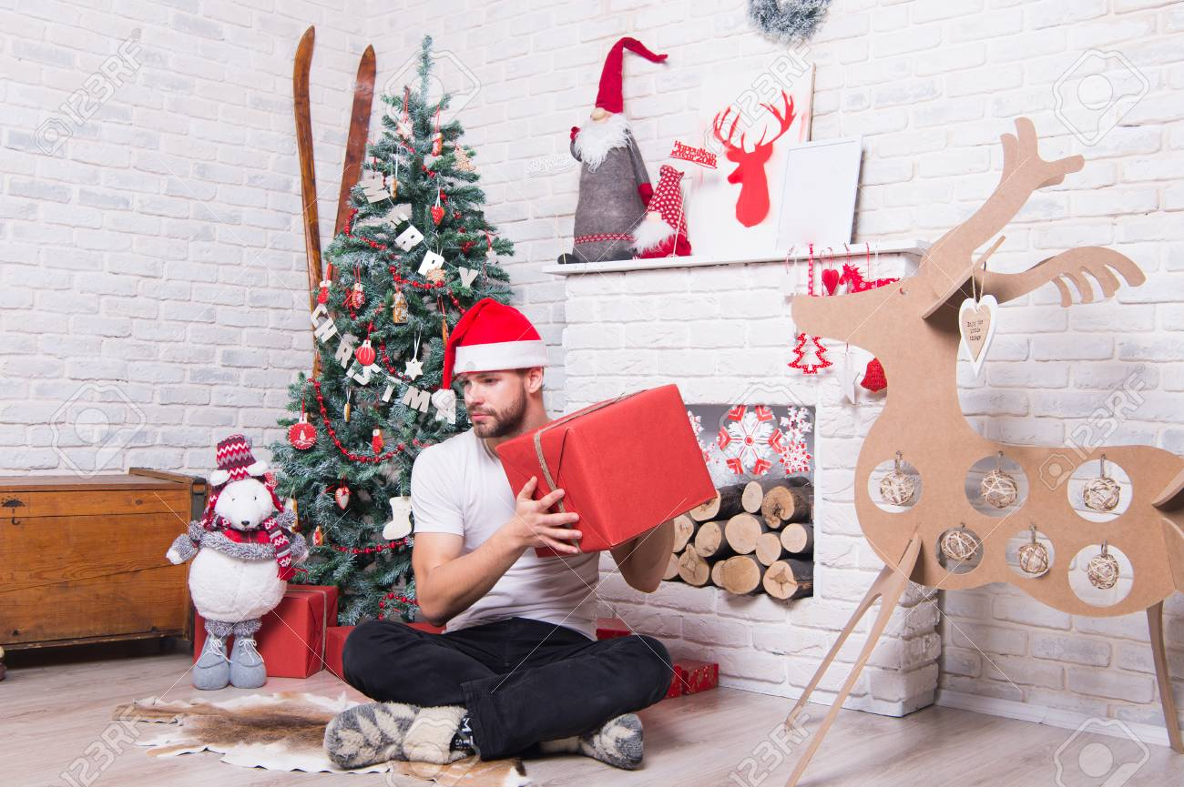 b036707d82003 Man in santa hat sit on floor at fireplace. Boxing day concept. Macho hold present  box at xmas tree. Christmas and new year
