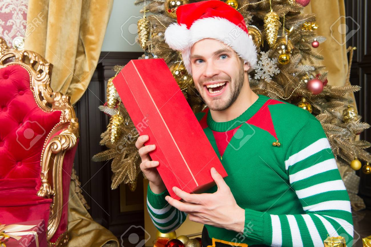 Macho in elf costume smile with box. Man in santa hat with present at Christmas  sc 1 st  123RF.com & Macho In Elf Costume Smile With Box. Man In Santa Hat With Present ...