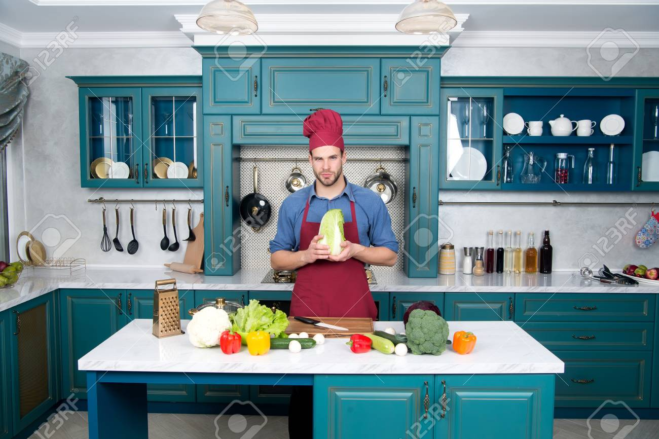 Guy In Chef Hat, Apron Hold Chinese Cabbage In Kitchen. Vegetables ...